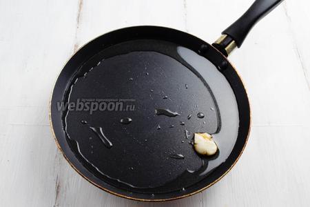 На сковородку влить растительное масло и немного дать ему прогреться. Зубчик чеснока очистить, расплющить ножом. Обжарить чеснок на масле в течение 2-3 минут. Чеснок немного ароматизирует масло.