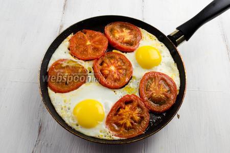 Перевернуть кружочки помидоров на другую сторону и сразу же влить яйца на сковороду. Жарить яичницу в течение 5 минут на малом огне. Следить, чтобы не подгорел белок.