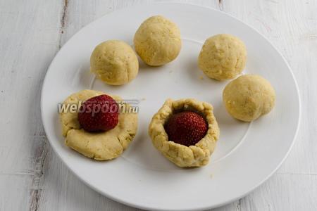 Отщипывая от общей массы небольшой кусок, скатать его в шар (размер шариков угадывайте по размеру ягод).  Расплющить шарик. Вложить в центр лепёшки ягоду клубники. Аккуратно облепить ягоду тестом и скатать в шарик.