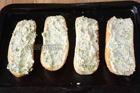 Мини-багеты разрезать вдоль на 2 части. Выложить на сухой противень. Смазать каждый багет сырной массой.