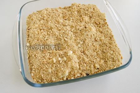 В форму с десертом выложите оставшуюся половину печенья, также покрошенного в мелкую крошку.