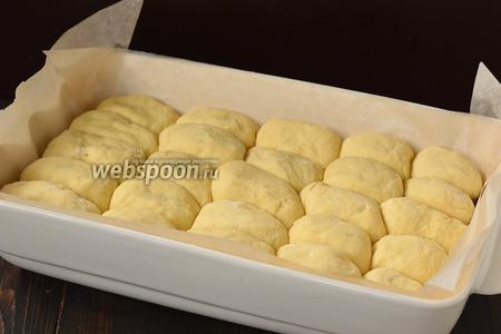 Сформировать пирожки и выложить плотно 1 к 1 в форму для выпечки. Накрыть полотенцем и оставить в тёплом месте на 25 минут.