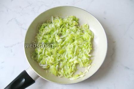 Налить на сковороду с луком-пореем и капустой немного воды и накрыть крышкой. Тушить на небольшом огне, периодически перемешивая. Посолить и поперчить по вкусу.