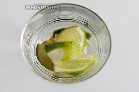 Лайм нарезаем на толстые пластинки, затем на дольки-четвертинки и поместим в стакан.