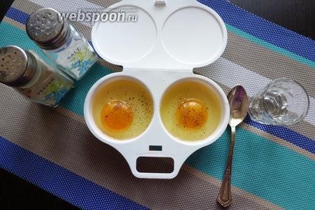 В каждую ячейку гаджета разбиваем яйцо. Посолим, посыплем перцем и вольём по 1-2 чайной ложки воды.