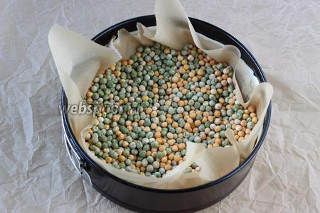 Тесто застелить бумагой для выпечки, насыпать сверху фасоль или горох, чтобы тесто не вздулось при выпечке и отправить в разогретую духовку (180°С) на 15 минут.