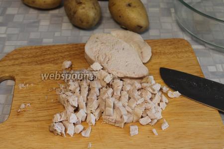 Отварить куриную грудку, добавив коренья и соль. Остудить и нарезать мелким кубиком.