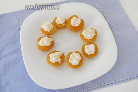 Кладём по 1 ложечке крема-фреш на половинки абрикосов.