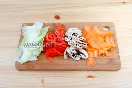 Подготавливаем овощи. Морковь и кабачок очищаем от кожуры и режем тонкими полосками с помощью картофелечистки. Перец нарезаем тонкой соломкой, а шампиньоны пластинками. Все ингредиенты должны быть тонко порезаны, чтобы они успели пропечься вместе с рыбой.