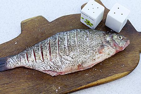 Сделайте надрезы по всему туловищу. Приправьте солью и молотым перцем со всех сторон и внутри. Оставьте на 20-30 минут.