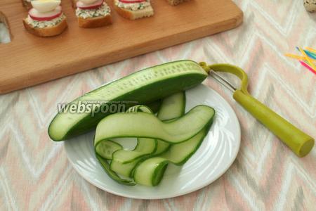 Огурцы нарезать тонкими слайсами с помощью овощечистки.