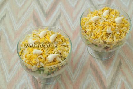 Яйца почистить и натереть на тёрке, выложить сверху лука и нанести майонез.