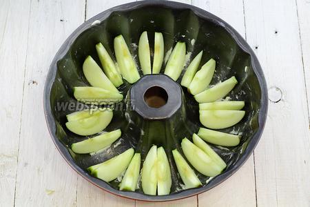 Форму для выпекания смажьте сливочным маслом. Уложите дольки яблока.