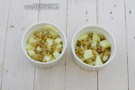 Порционные формочки смажьте сливочным маслом. На дно уложите нарезанное яблоко и белую смородину, свежую или замороженную.