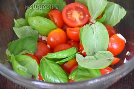 К помидорам добавить мелко нарезанный чеснок, листочки базилика, соль и хорошо перемешать.