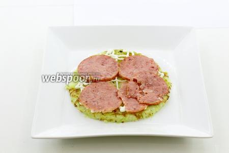 Сверху уложите тонкие кружочки колбасы.