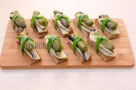 Теперь можно собирать нашу закуску. На каждый ломтик обжаренного хлеба положить картофельную полоску, сверху копчёную рыбку, затем корнишон. При желании можно хлеб натереть ещё чесноком. Перевязать каждый хлебец с начинкой полоской зелёного лука. Собирать тосты лучше всего перед подачей, поскольку важно, чтобы хлеб оставался хрустящим. Наши тосты со шпротами готовы.