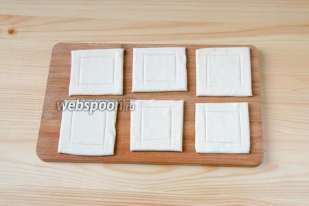 В первую очередь подготовим основу для закуски из слоёного теста. Для этого размороженное тесто раскатываем в пласт толщиной 2-3 мм. Режем его на квадраты и, отступив от края примерно 6 мм, по периметру каждого квадрата делаем неглубокие надрезы.