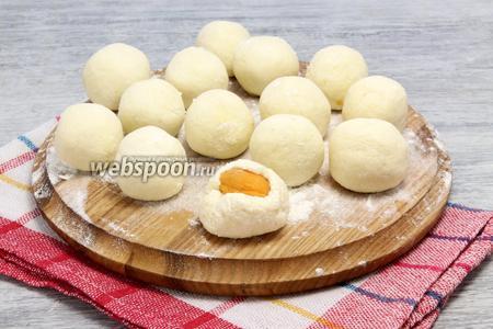 Из охлаждённого творожного теста делаем лепёшки, внутри помещаем абрикосы с сахаром, формируем шарики — полностью прячем начинку, обкатываем в муке.