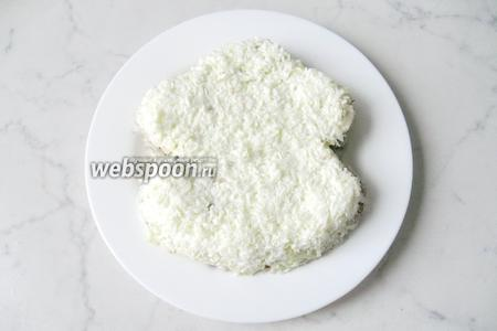 Сварите вкрутую яйца. Охладите и очистите. Отделите белки от желтков. Белки натрите на тёрке и выложите ими мордочку мартышки.