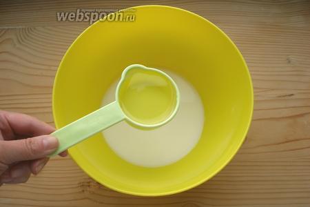 Молоко влить в глубокую миску. Добавить подсолнечное масло. Можно использовать и оливковое.