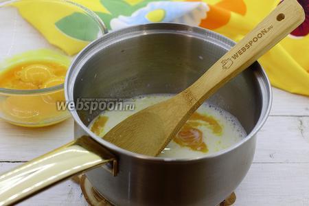 В горячее молоко добавьте куриные желтки. Интенсивно мешайте венчиком, чтобы желтки не превратились в хлопья.