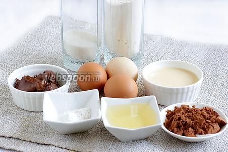 Для шоколадного бисквита возьмём яйца, какао, шоколадную пасту, сгущённое молоко, растительное масло, разрыхлитель, ванилин, сахар и муку.
