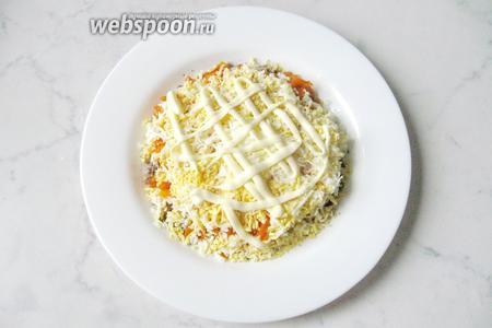 Покрыть измельчённые яйца сеткой майонеза.