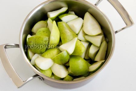 Груши промойте, разрежьте на части, удалите плодоножки и сердцевинки. Поместите ломтики груш в кастрюлю.