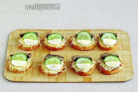 Поверх сыра разложить по 1 рыбке, по 1/4 яйца и по 1 половинке ломтика огурца. Готово!
