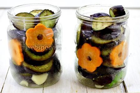 Добавьте кружочки баклажан. Для украшения вырежьте цветочки из моркови. Залейте баклажаны горячей кипячёной водой. Слейте в подходящую кастрюлю. Добавьте в воду соль, сахар, уксус. Доведите до кипения. Залейте маринадом баночки.