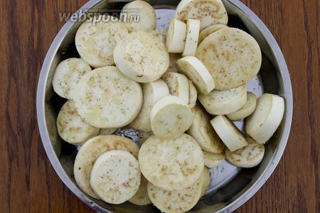 Баклажаны промойте, нарежьте кружочками толщиной примерно 7 мм. Посолите, добавьте итальянские травы, растительное масло. Перемешайте.