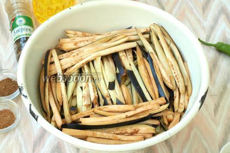 У баклажанов отрезать плодоножку и нарезать их вдоль тонкими полосками. Сложить в глубокую миску и хорошо посолить. Оставить баклажаны на 1 час.