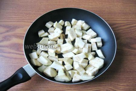 Баклажаны помыть, почистить и нарезать небольшими кубиками. Выложить на сковороду с подсолнечным маслом.