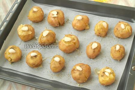 Сверху, на каждую картофелину, выложить по пластинке чеснока.