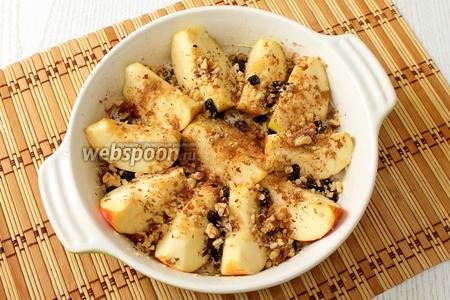 Выкладываем на яблоки измельчённые грецкие орехи и промытый изюм. Посыпаем молотой корицей по желанию.