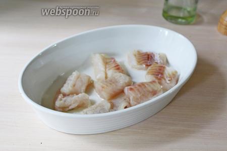 В смазанную оливковым маслом ёмкость выложить кусочки рыбы.
