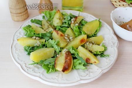Поверх салата выложить запечённый картофель и полить половиной соуса.