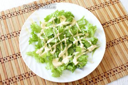 На тарелки выкладываем листья салата, которые рвём руками на кусочки. Поливаем соусом.