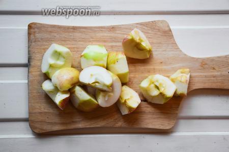 Налейте в кастрюлю воду и поставьте на огонь. Доведите практически до кипения. Яблоки очистите, нарежьте крупными дольками.
