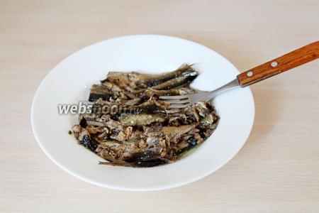 Для приготовления начинки из шпрот слить масло и рыбу размять вилкой.