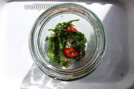 В чистую банку кладём лист смородины, укроп, морковную ботву, чеснок, по кусочку чили и сладкого перца.