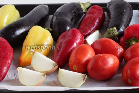 Овощи вымыть, у баклажан удалить чашелистики, лук разрезать на 4 части прямо в кожуре, перцы оставить целыми. Все овощи наколоть острым ножом, чтобы они не лопались в духовке и не брызгались от высокой температуры. Запечь их в духовке, примерно 25-30 минут, при 210-220°С. Овощи должны стать мягкими, а их корочка озолотиться и даже обуглиться.