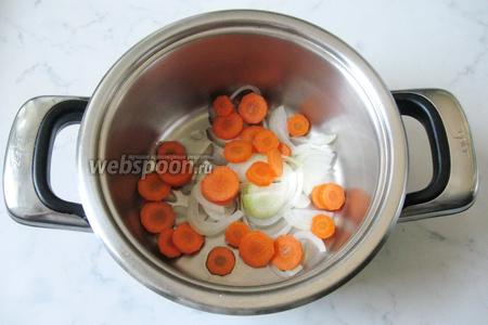 В кастрюлю с толстым дном налить подсолнечное масло. Выложить нарезанные лук и морковь.