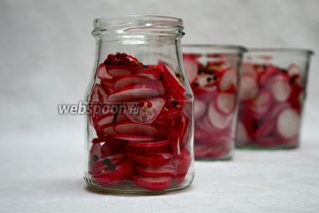 В подготовленные банки укладываем нарезанный редис и специи: чёрный и розовый перцы, горчичные зёрна и по 1 гвоздичке в каждую банку.