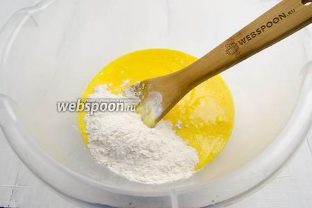 Вылить массу в глубокую посуду. Частями добавлять мучную смесь, замешивая тесто.