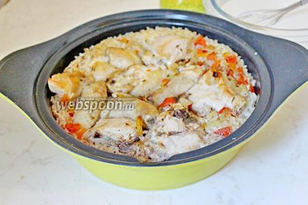 Вынимаем из духовки готовую курицу. Чеснок разрезать на 2 части и воткнуть в рис.