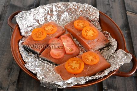 Разрежьте рыбное филе на порционные кусочки и выложите на фольгу. Можно обойтись и простой формой, но, как опытным путём выяснилось, к фольге крошки совершенно не прилипают, поэтому такой способ просто удобнее. На рыбу выложите тонкие ломтики помидоров, посолите и поперчите.