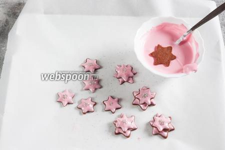 Вторыми идут средние звёздочки. Их точно так же обмакиваем в глазурь, а потом на них со сдвигом приклеиваем сверху маленькие звёздочки с «тычинками».