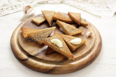 Все ещё горячие гренки из чёрного хлеба натираем чесночными зубками (с обоих боков).
